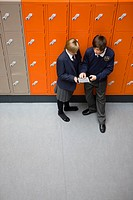 Students in school uniforms using digital tablet outside lockers in corridor