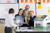 Teacher and students in school uniforms with wind turbine and solar panel models in science class