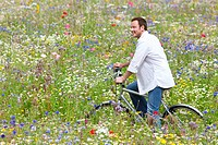 Smiling man riding bicycle in wildflower field