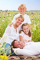 Portrait of smiling family relaxing in sunny wildflower field
