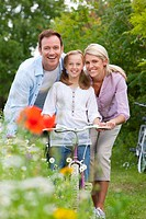 Portrait of smiling family with bicycle in field
