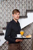 Waiter holding breakfast tray in cafe