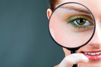 Close_up of young woman looking through magnifying glass