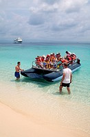 A small boat of tourists from the MS Yorktown Clipper lands on the white beach of Nia Tupu Island in the San Blas Islands of Panama.