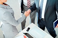 Image of business partners handshaking after signing contract