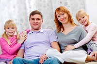 Image of friendly family with two daughters looking at camera