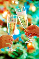 Close_up of hands holding flutes of champagne doing clink