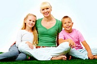 Portrait of happy family in casual clothes sitting on green grass