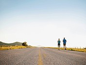 Mid adult couple running on empty road