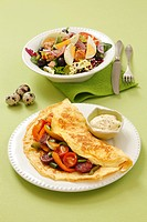 Omelette with chorizo and salad with eggs, olives and tuna