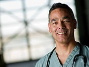 Doctor in medical scrubs smiling at camera