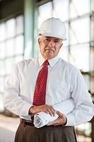 Portrait of senior man wearing tie and hardhat, holding blueprint