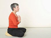 Senior woman sitting in prayer position