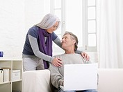 Germany, Hamburg, Senior couple with laptop looking at eachother, smiling (thumbnail)