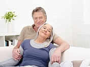 Germany, Hamburg, Senior couple resting on sofa, portrait