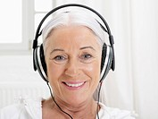 Germany, Hamburg, Senior woman listening music, smiling, portrait