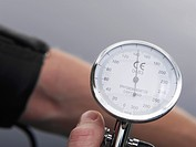 Human hand holding blood pressure gauge, close up