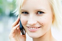 Germany, Bavaria, Munich, Young woman on phone, smiling, portrait