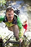 Germany, Upper Bavaria, Couple climbing ladder while hiking, smiling