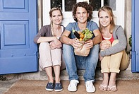 Italy, Tuscany, Magliano, Young man and women sitting on doorstep with vegetables, smiling, portrait