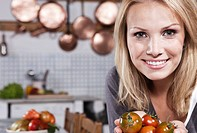 Italy, Tuscany, Magliano, Young woman holding tomatoes in kitchen, smiling, portrait