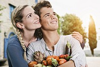 Italy, Tuscany, Magliano, Young man and woman holding different vegetables, smiling