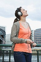 Germany, Berlin, Woman with headphones listening to music