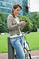 Germany, Berlin, Woman using cell phone besides bicycle