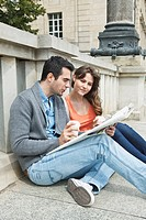 Germany, Berlin, Couple sitting on sidewalk and reading newspaper