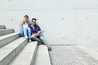 Germany, Berlin, Couple using laptop on stairway