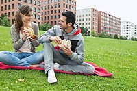 Germany, Berlin, Couple eating food in park