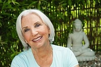 Germany, Bavaria, Senior woman smiling with buddha statue in background