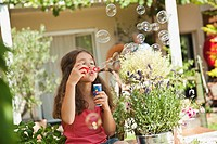 Germany, Bavaria, Girl blowing soap bubbles in garden