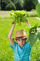 Germany, Bavaria, Boy in garden holding vegetables, smiling, portrait