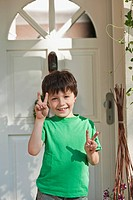 Germany, Bavaria, Boy showing peace sign, smiling, portrait