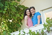 Germany, Bavaria, Couple in balcony, smiling, portrait