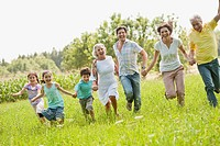 Germany, Bavaria, Family running together in grass at picnic