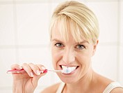 Close up of mature woman doing brushing her teeth, smiling, portrait