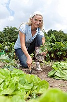 Germany, Bavaria, Altenthann, Woman gardening in garden, smiling, portrait