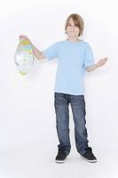Germany, Bavaria, Ebenhausen, Boy holding crushed inflatable globe against white background, portrait