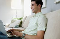 Man with laptop in living room (thumbnail)