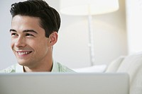 Portrait of young smiling man with laptop