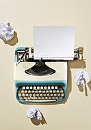 Studio shot of old_fashioned typewriter and paper balls