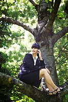 Businesswoman on cell phone in tree