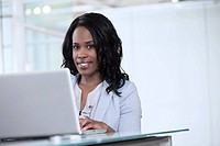 Portrait of business woman using laptop in office