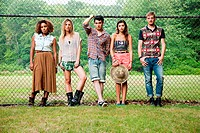 Portrait of friends standing against chain link fence