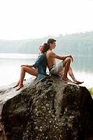 Young couple leaning on each other on rock