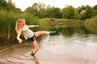 Teenage girl wading into the middle of a lake with over_flowing wellies