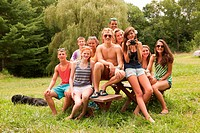 Teenagers relaxing together, sitting on a picnic table in the countryside