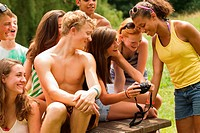 Teenagers reviewing photos together on a friend's camera
